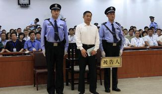 Former high-flying Chinese politician Bo Xilai (center), who was tried last month on charges of taking bribes, embezzlement and abuse of power, appears in court in Jinan, in eastern China's Shandong province, on Sunday, Sept. 22, 2013, where he was sentenced to life in prison. (AP Photo/Jinan Intermediate People's Court)