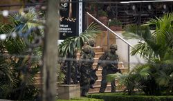 ** FILE ** Soldiers from the Kenya Defense Forces carry a wounded colleague out of the Westgate Mall in Nairobi, Kenya, on Sunday, Sept. 22, 2013, following the sound of explosions and gunfire. (AP Photo/Ben Curtis)