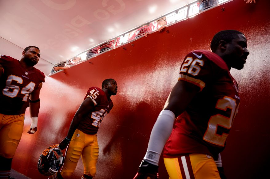 Washington Redskins defensive end Kedric Golston (64), Washington Redskins defensive back Jerome Murphy (45) and Washington Redskins cornerback Josh Wilson (26) head to the locker room before the Washington Redskins play the Detroit Lions in NFL football at FedExField, Landover, Md., Monday, September 9, 2013. (Andrew Harnik/The Washington Times)