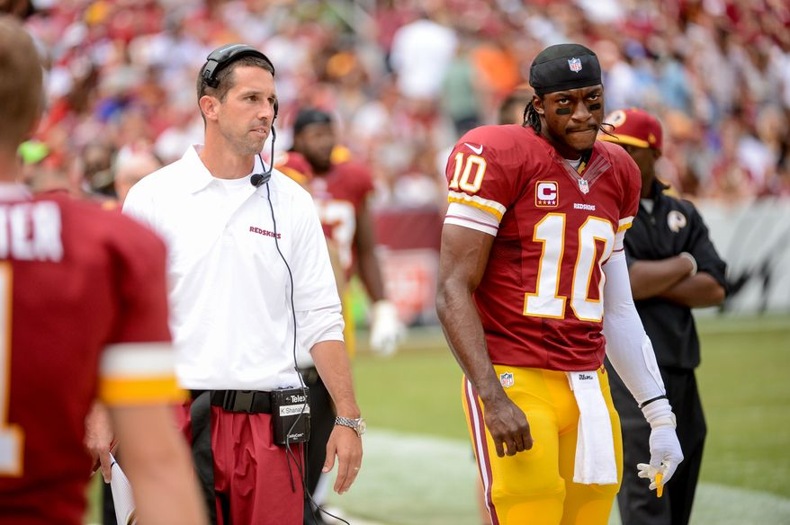 Washington Redskins offensive coordinator Kyle Shanahan, left, talks with Washington Redskins quarterback Robert Griffin III (10) on the sideline after Griffin threw an interception in the second quarter as the Washington Redskins play the Detroit Lions in NFL football at FedExField, Landover, Md., Monday, September 9, 2013. (Andrew Harnik/The Washington Times)