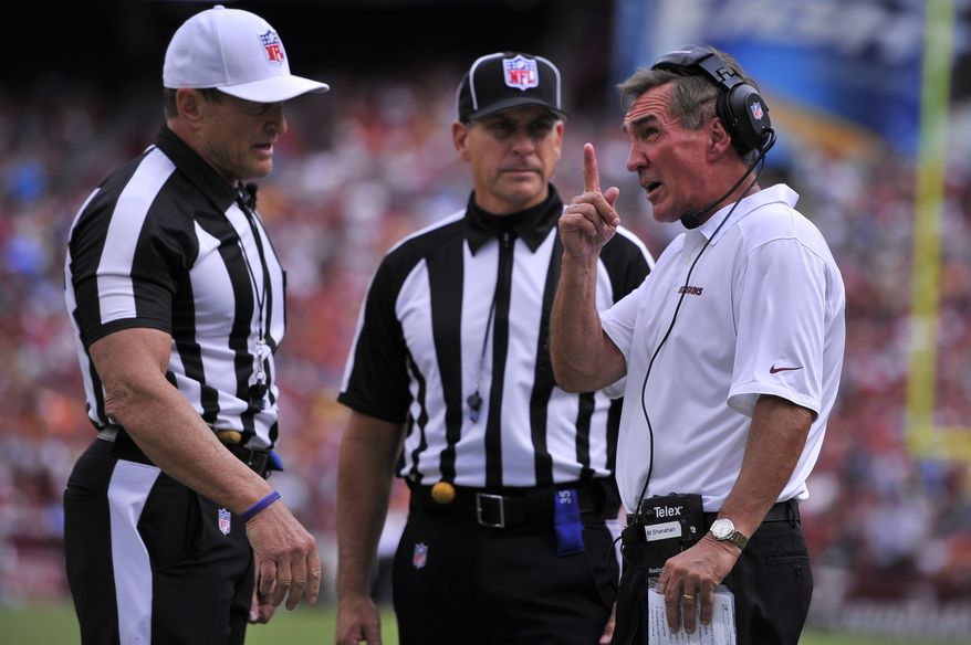 Washington Redskins head coach Mike Shanahan argues a second-quarter holding call with referee Ed Hochuli (L)as the Washington Redskins play the Detroit Lions at FedExField, Landover, Md., September 22, 2013. (Preston Keres/Special for The Washington Times)