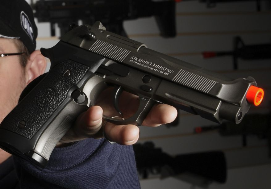 **FILE** Jason Pfingsten, owner of Pacific Rim Airsoft, Ltd., shows a airsoft semi-automatic pistol designed to look like a real Beretta at his Seattle store on Feb. 13, 2008. (Associated Press/Andy Rogers, Seattle Post-Intelligencer)