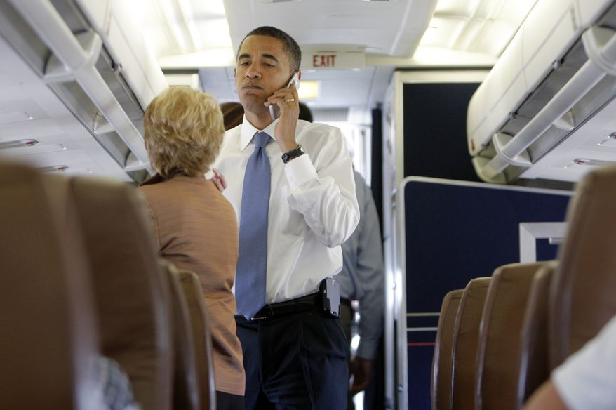 **FILE** Then-Democratic presidential candidate Barack Obama talks on the phone aboard his campaign plane after landing in St. Louis on July 7, 2008. (Associated Press)