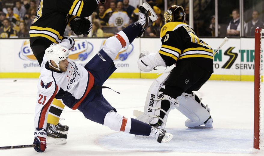 Washington Capitals center Brooks Laich (21) is upended by Boston Bruins defenseman Zdeno Chara, rear left, as he clears the crease in front of Bruins goalie Tuukka Rask during the first period of an NHL hockey game, Monday, Sept. 23, 2013, in Boston. (AP Photo/Charles Krupa)