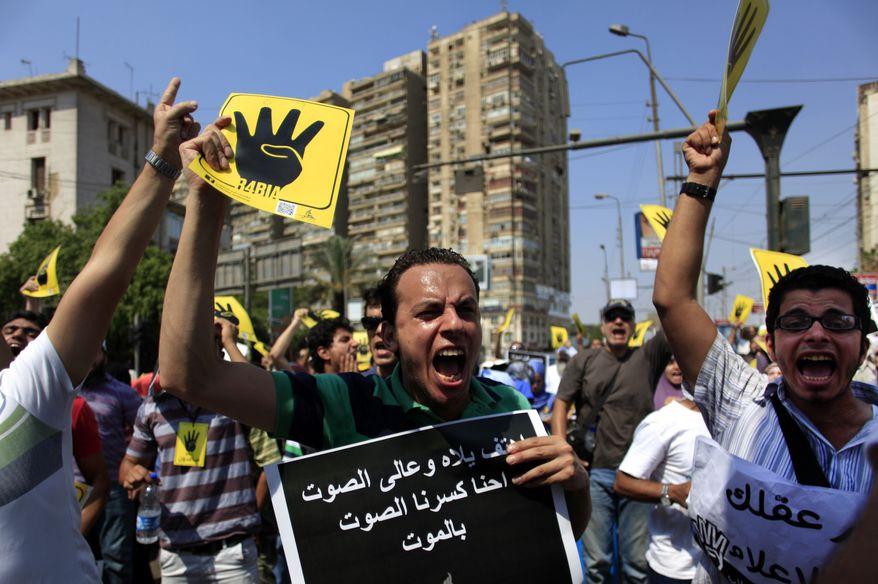 ** FILE ** Supporters of Egypt's ousted President Mohammed Morsi chant slogans and hold placards showing an open palm with four raised fingers, which has become a symbol of the Rabaah al-Adawiya mosque, where Morsi supporters had held a sit-in for weeks that was violently dispersed on Aug. during a protest in Cairo, Egypt, Friday, Sept. 6, 2013. (AP Photo/Khalil Hamra)