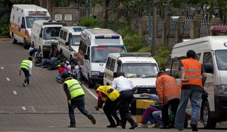 """Paramedics run beside parked ambulances outside the Westgate Mall in Nairobi after heavy shooting started for the third time since the morning Monday, Sept. 23, 2013. Kenya's military launched a major operation at the upscale Nairobi mall and said it had rescued """"most"""" of the hostages being held captive by al-Qaeda-linked militants during the standoff. (AP Photo/Sayyid Azim)"""