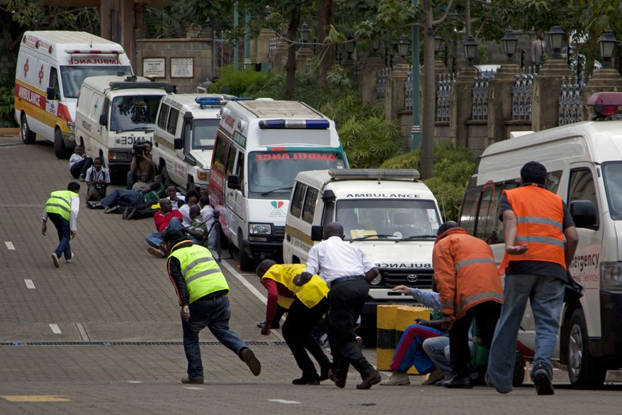 """Security personnel take cover outside the Westgate Mall in Nairobi, Kenya, after shooting started inside the building early on Monday, Sept. 23, 2013. Kenya's military launched a major operation at the upscale shopping center and said it had rescued """"most"""" of the hostages being held captive by al-Qaeda-linked militants during the standoff.  (AP Photo/Sayyid Azim)"""