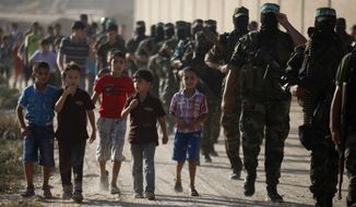 Masked Palestinian members of the Ezz Al-Din Al Qassam militia, the military wing of Hamas, march in the Nuseirat refugee camp in the central Gaza Strip on Friday, Sept. 20, 2013. (AP Photo/Hatem Moussa)