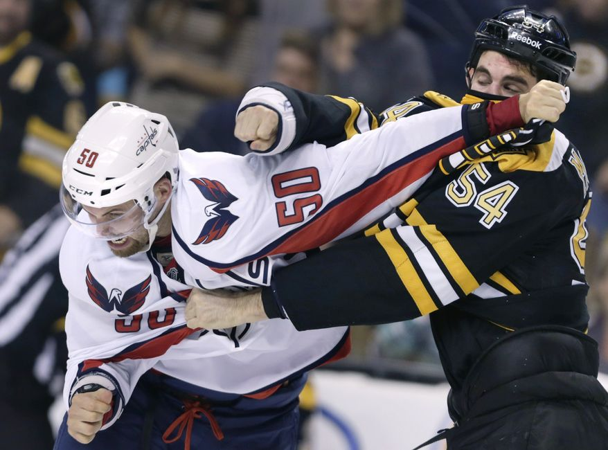 Washington Capitals left wing Dane Byers (50) tries to duck a punch from Boston Bruins defenseman Adam McQuaid (54) in the third period of an NHL preseason hockey game, Monday, Sept. 23, 2013, in Boston. The Bruins defeated the Capitals 3-2 in overtime. (AP Photo/Charles Krupa)