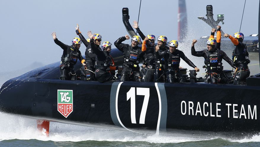 Crew memebers on Oracle Team USA celebrate after crossing the finish line during the 18th race of the America's Cup sailing event against Emirates Team New Zealand, Tuesday, Sept. 24, 2013, in San Francisco. Oracle Team USA won races 17 adn 18 to pull even with Emirates Team New Zealand. (AP Photo/Ben Margot)