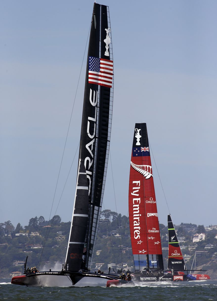 Oracle Team USA, left, prepares for the 17th race of the America's Cup sailing event against Emirates Team New Zealand, right, Tuesday, Sept. 24, 2013, in San Francisco. Oracle Team USA won both races Tuesday, evening the series. (AP Photo/Ben Margot)
