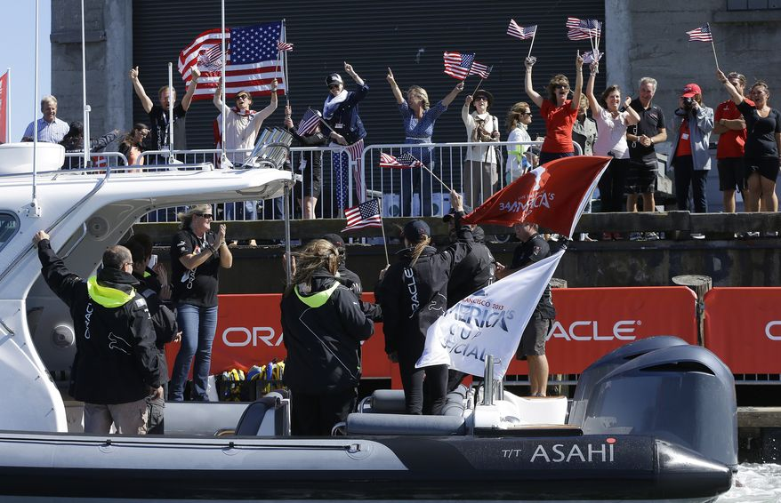 Fans cheer as a boat carrying Oracle CEO Larry Ellison passes a pier after Oracle Team USA defeated Emirates Team New Zealand in the 18th race of the America's Cup sailing event Tuesday, Sept. 24, 2013, in San Francisco. Oracle Team USA won both races Tuesday to even the series. (AP Photo/Ben Margot)