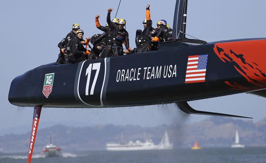 The crew on Oracle Team USA waves after winning the 17th race of the America's Cup sailing event against Emirates Team New Zealand, Tuesday, Sept. 24, 2013, in San Francisco. Oracle Team USA won both races Tuesday to even the series. (AP Photo/Ben Margot)