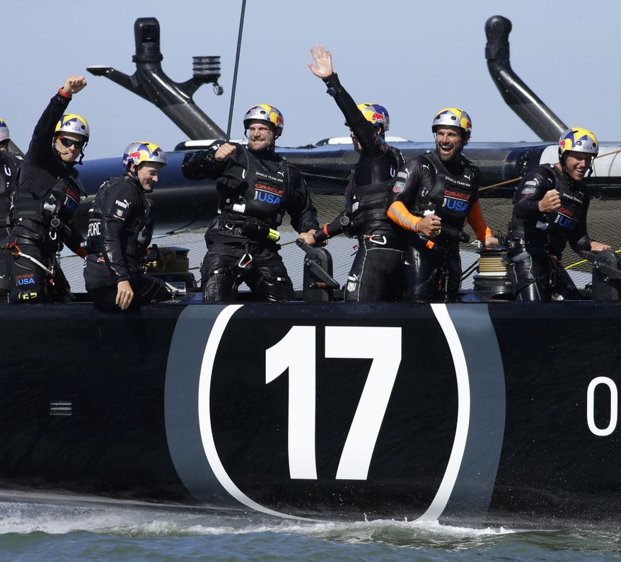 The crew on Oracle Team USA celebrates after crossing the finish line during the 18th race of the America's Cup sailing event against Emirates Team New Zealand, Tuesday, Sept. 24, 2013, in San Francisco. Oracle Team USA won races 17 and 18 to pull even with Emirates Team New Zealand. At left is skipper Jimmy Spithill. (AP Photo/Ben Margot)