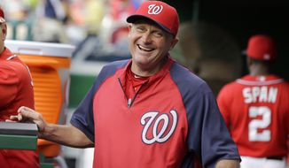 Washington Nationals bench coach Randy Knorr (53) laughs in the dugout before a baseball game against the Philadelphia Phillies at Nationals Park Saturday, Aug. 10, 2013, in Washington. (AP Photo/Alex Brandon)