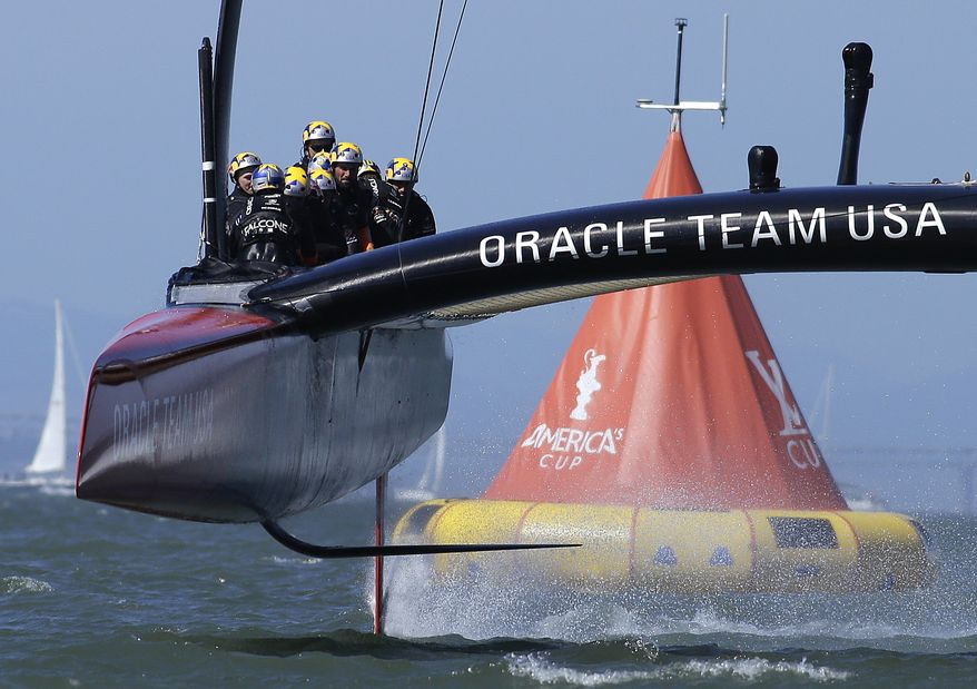 Oracle Team USA crosses the finish line during the 18th race of the America's Cup sailing event against Emirates Team New Zealand on Tuesday, Sept. 24, 2013, in San Francisco. Oracle Team USA won both races Tuesday to even the series. (AP Photo/Ben Margot)