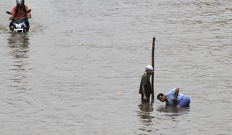 Indians clean blocked sewerage line to drain out flooded water from a road after heavy rains lashed, in Ahmadabad, India, Wednesday, Sept. 25, 2013. Massive flooding has forced 15,000 people to evacuate villages in the west Indian state of Gujarat where heavy rains and swollen rivers have inundated cities and closed off roads and railway lines. (AP Photo/Ajit Solanki)