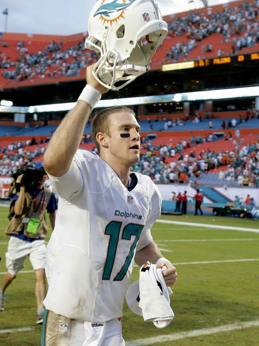 In this Sept. 22, 2013, file photo, Miami Dolphins quarterback Ryan Tannehill holds up his helmet to fans as he runs off the field after the Dolphins defeated the Atlanta Falcons 27-23 in an NFL football game in Miami Gardens, Fla. With a flair for the dramatic, the second-year prol has taken command at quarterback, solving the Dolphins' perennial problem at the position and leading them to a surprising 3-0 start. (AP Photo/Wilfredo Lee, File)