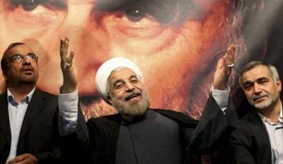 ** FILE ** In front of a portrait of the late Iranian revolutionary founder Ayatollah Khomeini, presidential candidate Hasan Rowhani, a former top nuclear negotiator, center, gestures to his supporters at a rally in Tehran, Iran, Saturday, June 1, 2013.
