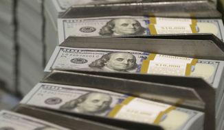 Just-cut stacks of $100 bills make their way down the production line at the Bureau of Engraving and Printing's Western Currency Facility in Fort Worth, Texas, on Tuesday, Sept. 24, 2013. (Associated Press) ** FILE **