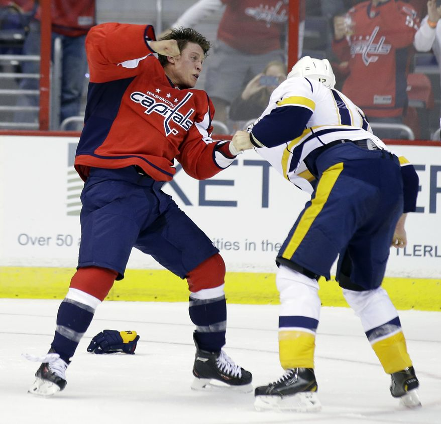 Washington Capitals defenseman Steven Oleksy (61) fights with Nashville Predators center Mike Fisher (12) in the second period of a preseason NHL hockey game, Wednesday, Sept. 25, 2013, in Washington. The Capitals won 4-1. (AP Photo/Alex Brandon)