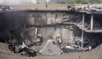 ** FILE ** This photo released by the Kenya Presidency shows the collapsed upper car park of the Westgate Mall in Nairobi, Kenya, Thursday, Sept. 26, 2013. Working near bodies crushed by rubble in a bullet-scarred, scorched mall, FBI agents continued fingerprint, DNA and ballistic analysis to help determine the identities and nationalities of victims and al-Shabab gunmen who attacked the shopping center, killing more than 60 people. (AP Photo/Kenya Presidency)
