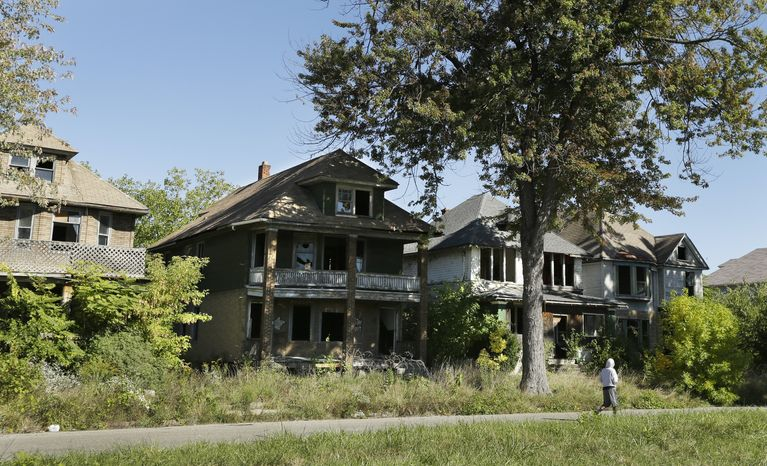 A young man walks in front of a row of abandoned houses in Detroit, Thursday, Sept. 26, 2013. Four of President Barack Obama's top advisers will converge on Detroit Friday to meet privately with state and local leaders about ways the federal government can help the bankrupt city short of a bailout. The White House said Thursday that top economic adviser Gene Sperling will join U.S. Attorney General Eric Holder, Transportation Secretary Anthony Foxx and HUD Secretary Shaun Donovan in the closed meeting. (AP Photo/Carlos Osorio)