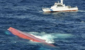 In this aerial photo, a capsized Japanese freighter Eifuku-Maru No.18 (foreground) as a Japan Coast Guard patrol boat conducts a search operation for missing crew members including the skipper and deputy skipper of the ship, off Izu Oshima, Japan, on Sept. 27, 2013. The ship crashed with the Sierra Leone-registered Jia Hui. (Associated Press/Kyodo News)