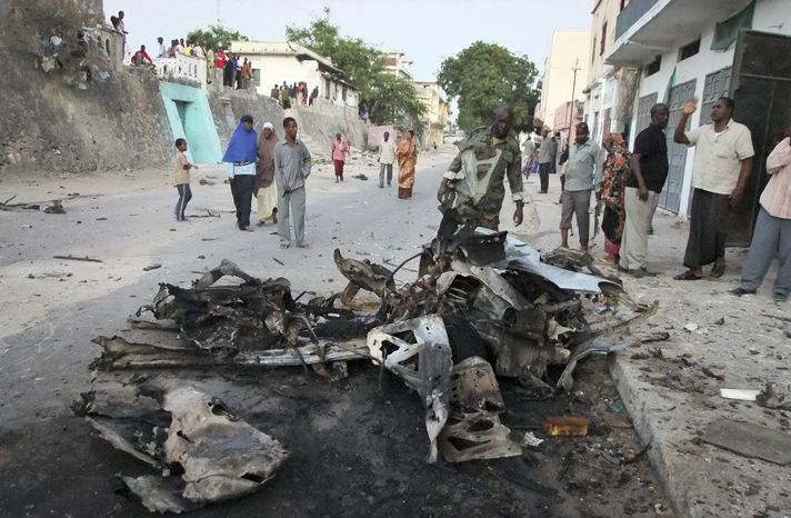 ** FILE ** Somalis observe the remains of a vehicle used in a car bomb attack in the capital Mogadishu, Somalia in this Wednesday, Feb. 8, 2012 file photo, an attack claimed by a spokesman for Somalia's al-Shabab Islamist insurgency. Al-Shabab have claimed responsibility for the gun and grenade attack on a shopping mall in Nairobi, Kenya, Saturday, Sept 21, which has left dozens dead and wounded, apparently in retaliation for Kenya's military participation in peace-keeping efforts in Somalia.(AP Photo/Farah Abdi Warsameh, file)