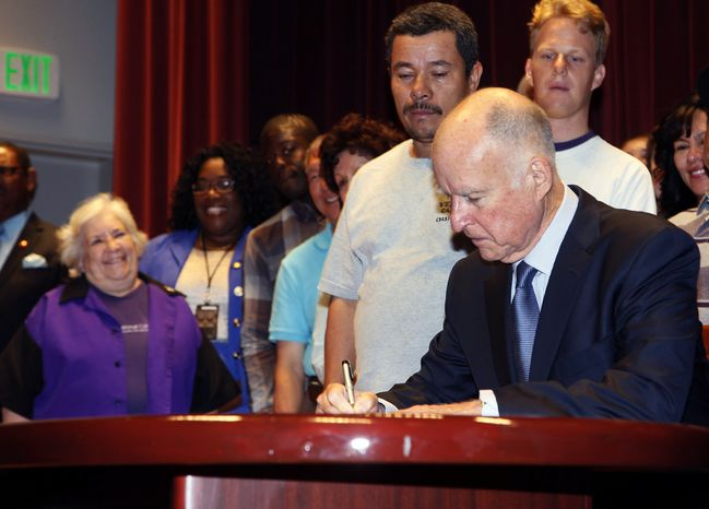 California Gov. Jerry Brown signs a bill to raise California minimum wage in Los Angeles Wednesday, Sept. 25, 2013. Brown has put his signature on a bill that will hike California's minimum wage to