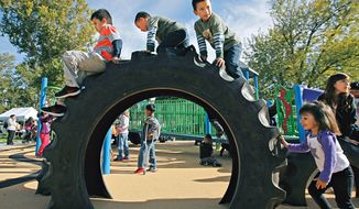 "Children play on the new ""Tread Town"" playground during the grand opening of the certified Boundless Playground at Memorial Park in Pasco, Wash. (AP Photo/Tri-City Herald, Kai-Huei Yau) ** FILE **"