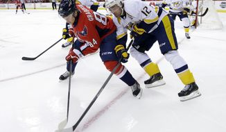 Washington Capitals center Mikhail Grabovski (84) battles for the puck with Nashville Predators center Mike Fisher (12) during the first period of a preseason NHL hockey game on Wednesday, Sept. 25, 2013, in Washington. The Capitals won 4-1. (AP Photo/Alex Brandon)