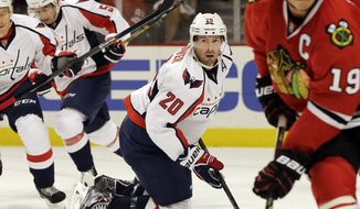 Washington Capitals' Troy Brouwer (20) watches the puck during the first period of an NHL preseason hockey game against the Chicago Blackhawks in Chicago, Saturday, Sept. 28, 2013. (AP Photo/Nam Y. Huh)