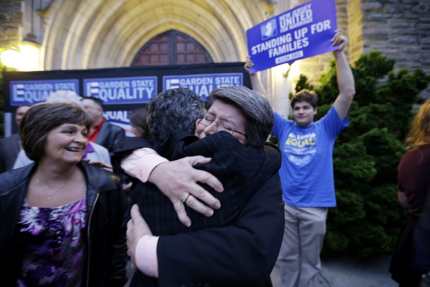 Cindy Meneghin, center right,, hugs her attorney Hayley Gorenberg, center left, during a  rally at Garden State Equality in Montclair, N.J., hours after same-sex marriages were made legal by a state judge, Friday, Sept. 27, 2013. (AP Photo/Julio Cortez)