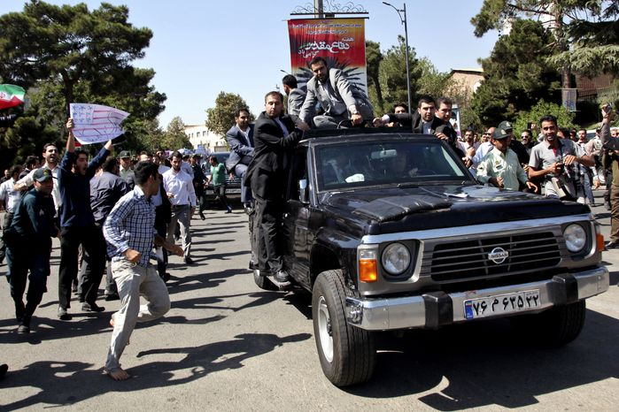 A protester (left) approaches Iranian President Hassan Rouhani's car as it leaves Mehrabad Airport after the leader's arrival in Tehran from the United States on Saturday, Sept. 28, 2013. (AP Photo/Ebrahim Noroozi)
