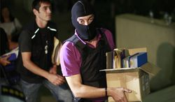 An anti-terror police officer carries a box containing the case file against the arrested suspects of the extreme far-right Golden Dawn party as he arrives at the court in Athens on Saturday, Sept. 28, 2013. Police arrested the leader and other top members of the party on Saturday in an escalation of a government crackdown after a fatal stabbing allegedly committed by a supporter. It is the first time since 1974 that sitting members of Parliament have been arrested. (AP Photo/Kostas Tsironis)