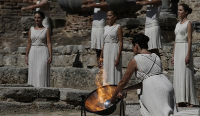 Actress Ino Menegaki, portraying a high priestess, lights the Olympic Flame for the 2014 Sochi Winter Games from the sun's rays during a ceremony at Ancient Olympia in southwestern Greece on Sunday, Sept. 29, 2013.  (AP Photo (AP Photo/Dimitri Messinis)