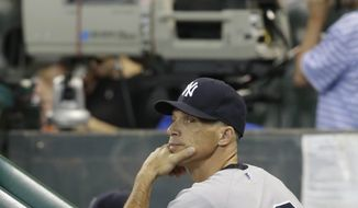 New York Yankees manager Joe Girardi watches the scoreboard from the dugout as the Yankees play the Houston Astros during a baseball game Sunday, Sept. 29, 2013, in Houston. The Yankees won the game 5-1 in 14 innings. (AP Photo/Richard Carson)