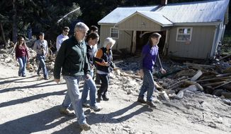 Senator Mark Udall, at left, walks through the flood damage with Jamestown mayor Tara Schoendinger, and Boulder County Commissioners Deb Gardner and Elise Jones in Jamestown on Saturday, Sept. 28, 2013. (AP Photo/Daily Camera, Jeremy Papasso)
