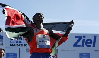 Wilson Kipsang from Kenya celebrates winning the 40th Berlin Marathon in Berlin on Sunday, Sept. 29, 2013, with a new world record of 2 hours, 3 minutes, 23 seconds. (AP Photo/Michael Sohn)