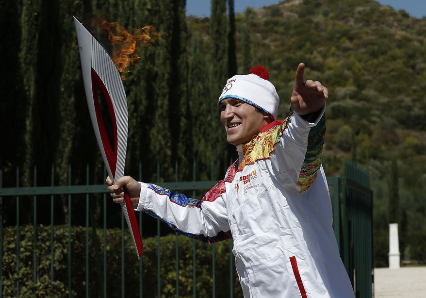 Second torchbearer Alexander Ovechkin of Russia, professional ice hockey winger and captain of the Washington Capitals, leaves the monument of Pierre de Coubertin during the torch relay after the ceremony of lighting of the Olympic flame at Ancient Olympia, in west southern Greece on Sunday  Sept. 29, 2013. The flame will be transported by torch relay to the Russian resort of Sochi, which will host the Feb. 7-23, 2014 Winter Olympics. (AP Photo/Dimitri Messinis, Pool)