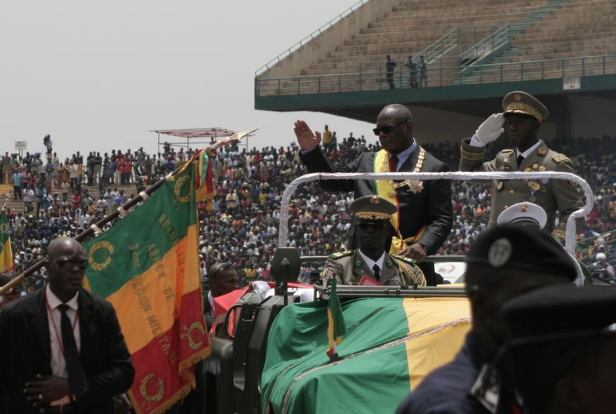 ** FILE ** Malian President Ibrahim Boubacar Keita (standing, second from right) waves to supporters as he arrives for his inauguration festivities in Bamako, Mali, on Thursday, Sept. 19, 2013. French President Francois Hollande, speaking at the event, declared that the war on terror had been won in Mali and listed the towns that French and Malian troops liberated from al Qaeda's local fighters earlier this year. (AP Photo/Harouna Traore)