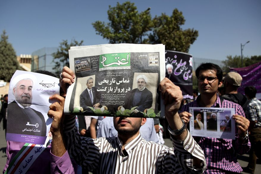 """A supporter of Iranian President Hassan Rouhani holds a local newspaper with a headline that reads, """"Historic call from a return flight,"""" upon the leader's arrival from the U.S. on Saturday, Sept. 28, 2013, near the Mehrabad Airport in Tehran. Iranians from across the political spectrum hailed the historic phone conversation between President Obama and Mr. Rouhani, reflecting wide support for an initiative that has the backing of both reformists and the country's conservative clerical leadership. (AP Photo/Ebrahim Noroozi)"""