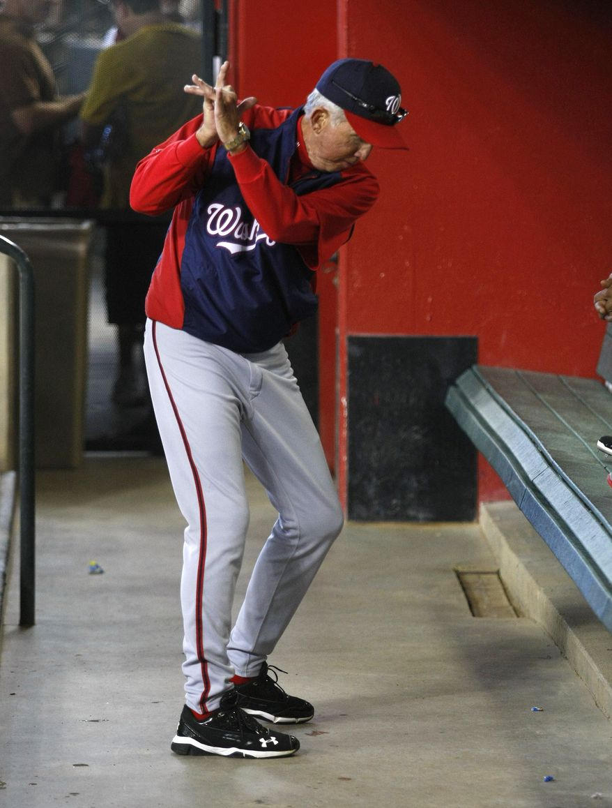 Washington Nationals manager Davey Johnson (5) practices his golf swing before an MLB National League baseball game against the Arizona Diamondbacks on Sunday, Sept 29, 2013, in Phoenix. Johnson announced he will retire at the end of this season. (AP Photo/Rick Scuteri)