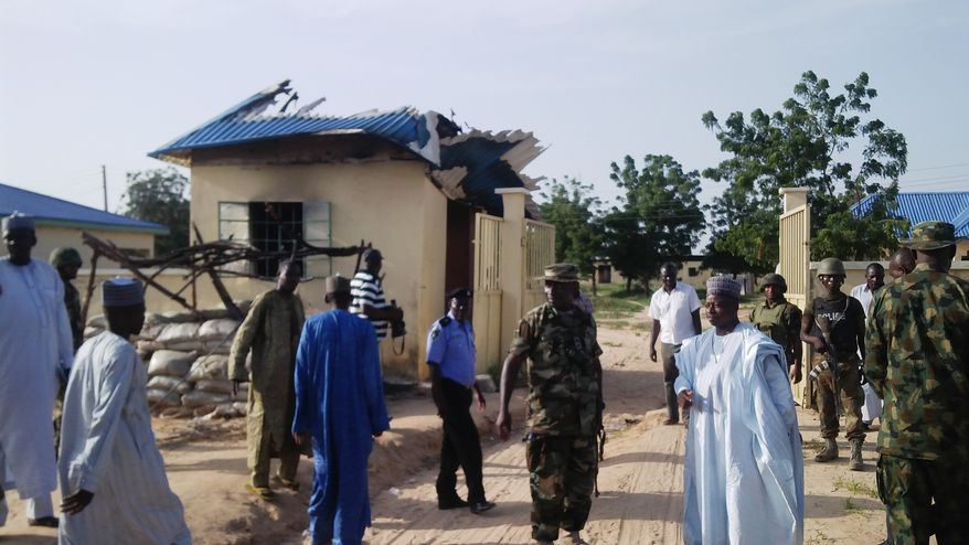 Government officials stand by a damaged house following an attack by Boko Haram in Benisheik, Nigeria, on Thursday, Sept. 19, 2013. Searching roadsides, bushes and fields, environmental agency workers have recovered the bodies of more than 100 civilians killed by suspected extremists, an official said of one of the highest death tolls in an Islamic uprising in northeast Nigeria. (AP Photo/Abdulkareem Haruna)