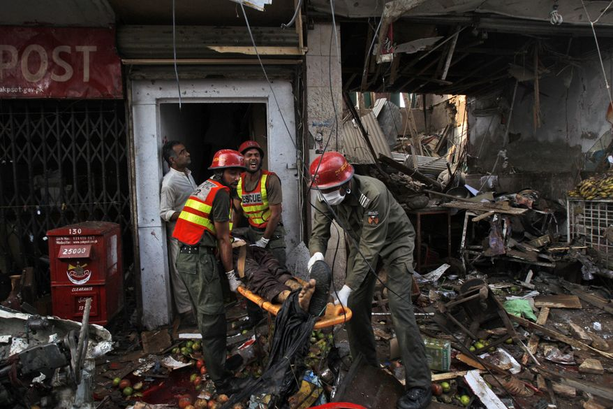 Rescue workers evacuate an injured man from the site of a car bomb blast in Peshawar, Pakistan, on Sunday, Sept. 29, 2013. The deadly car bomb exploded on a crowded street in the third blast to hit the troubled city in a week, officials said. (AP Photo/Mohammad Sajjad)