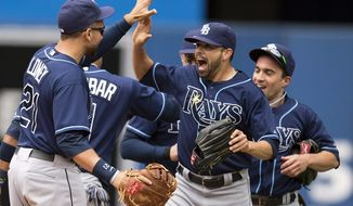 Tampa Bay Rays James Loney, left, Matt Joyce, center, and Sam Fuld, right, celebrate after the Rays defeated the Toronto Blue Jays 7-6 in a baseball game in Toronto on Sunday, Sept. 29, 2013. (AP Photo/The Canadian Press, Frank Gunn)
