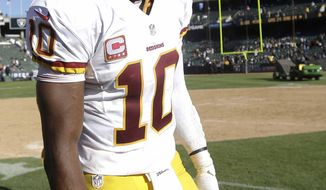 Washington Redskins quarterback Robert Griffin III (10) smiles after an NFL football game against the Oakland Raiders in Oakland, Calif., Sunday, Sept. 29, 2013. The Redskins won 24-14. (AP Photo/Marcio Jose Sanchez)