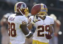 Washington Redskins running back Roy Helu Jr. (29) celebrates with wide receiver Pierre Garcon (88) after running for a 14-yard touchdown against the Oakland Raiders during the fourth quarter of an NFL football game in Oakland, Calif., Sunday, Sept. 29, 2013. The Redskins won 24-14. (AP Photo/Ben Margot)