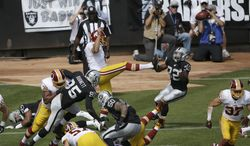 Washington Redskins punter Sav Rocca, center, has his punt blocked by Oakland Raiders' Rashad Jennings, bottom left, as Jeremy Stewart (32) prepares to recover during the first quarter of an NFL football game in Oakland, Calif., Sunday, Sept. 29, 2013. Stewart scored a touchdown. (AP Photo/Marcio Jose Sanchez)